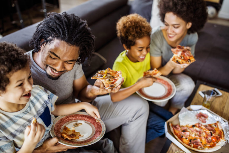 Happy African American family eating pizza at home.