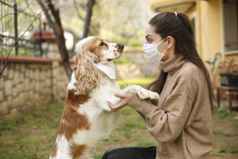 womand in mask with dog