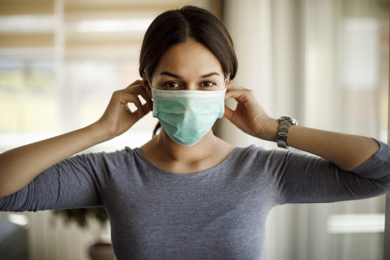 Portrait of young woman putting on a protective mask for coronavirus isolation