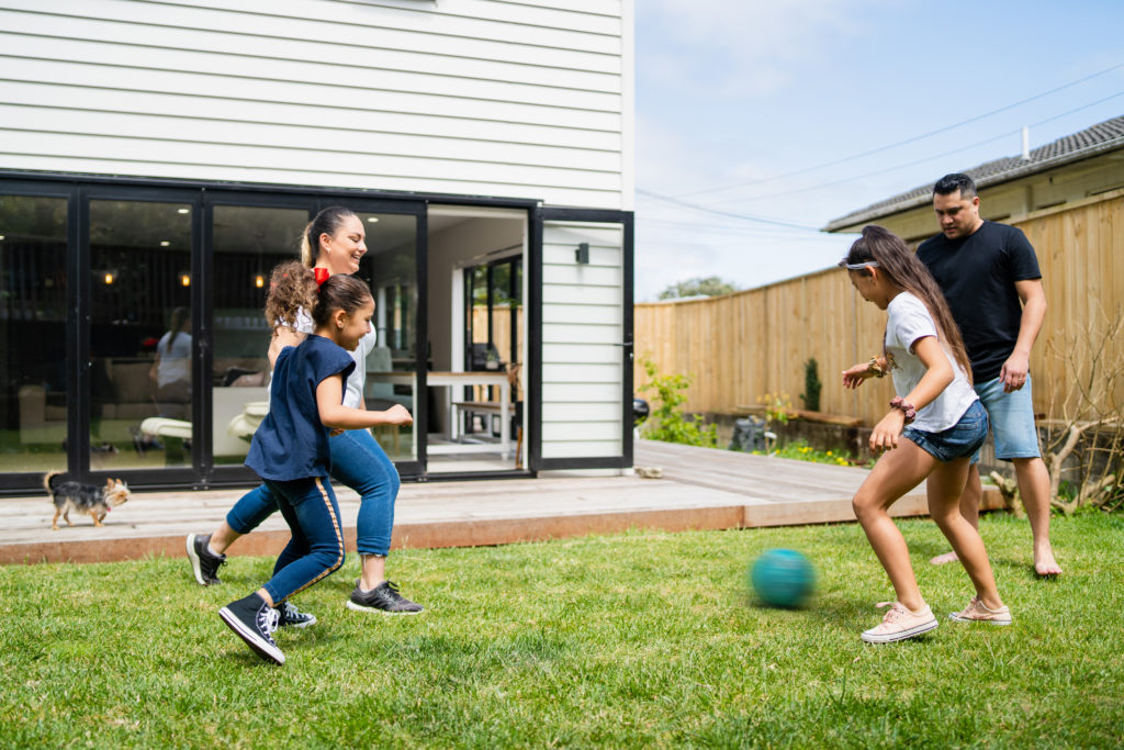 Parents playing soccer with kids in backyard.