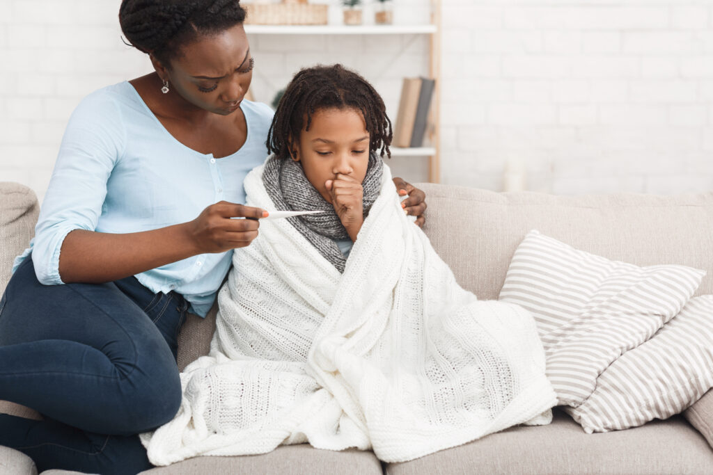 Caring African Mom Checking Temperature Of Her Sick Child At Home, Girl In Blanket
