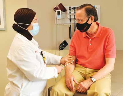 Neurologist Evren Burakgazi-Dalkilic, MD, with a patient.