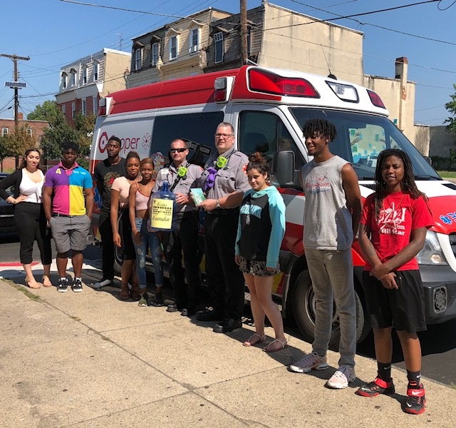 EMTs Zach Ewan and Charlie Brown are shown with student interns in front of Hopeworks N Camden offices on State Street in Camden, NJ.