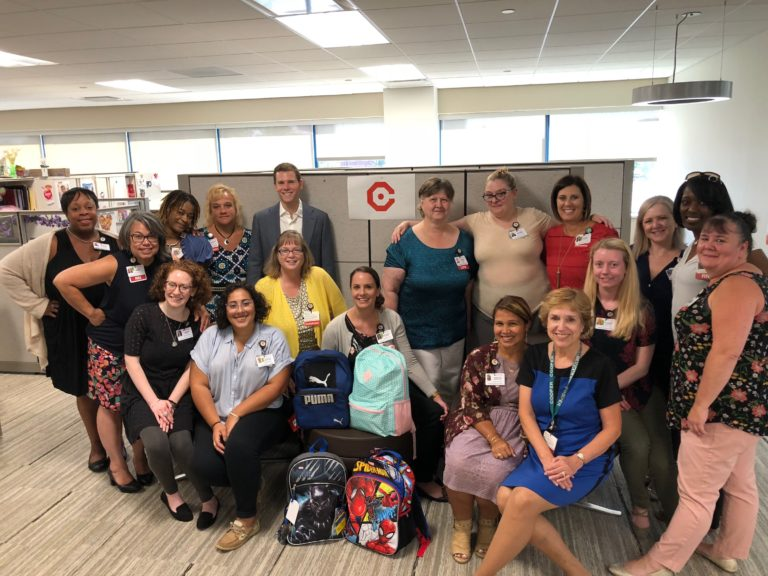 Our Population Health team posing with their donated backpacks! Photo credit: Max Kursh, Population Health.
