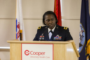 Brigadier General Telita Crosland, commanding general, Regional Health Command-Atlantic at podium with Cooper logo