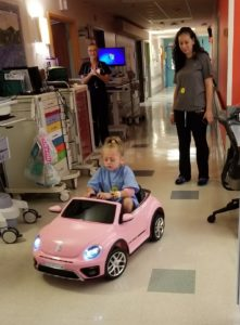 little girl drives car down hallway